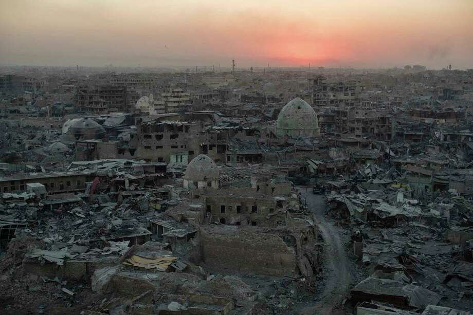 The sun sets behind destroyed buildings in western Mosul, Iraq. The fight to root out the Islamic State damaged or destroyed nearly a third of the historic Old City, and fewer than a tenth of the 730,000 people who fled western Mosul have returned. Photo: Felipe Dana, STF / Copyright 2017 The Associated Press. All rights reserved.