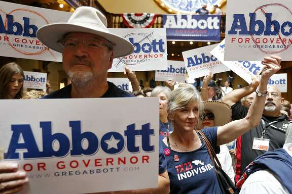 The author, Janet Oglethorpe (center), and others hold signs during an event where Gov. Abbott announced his bid for re-election at Sunset Station.
