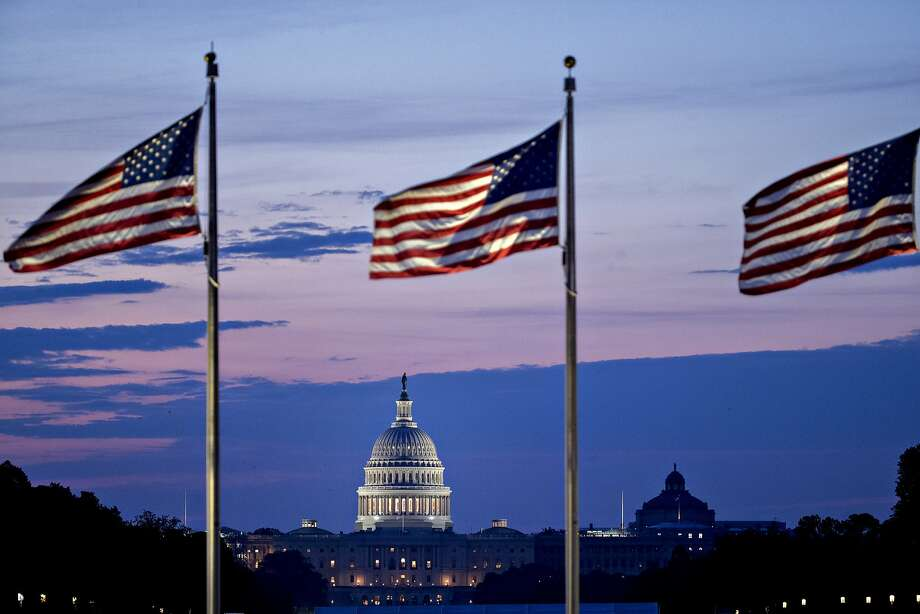 The U.S. Capitol stands beyond American flags before sunrise in Washington, D.C. Photo: Andrew Harrer, Bloomberg