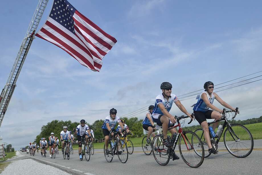 Riders in the Cops Cycling for Survivors fundraiser pass beneath the American flag as they make a stop at Jefferson Cemetery near Upland, Ind., on Tuesday. Photo: Jeff Morehead, Associated Press