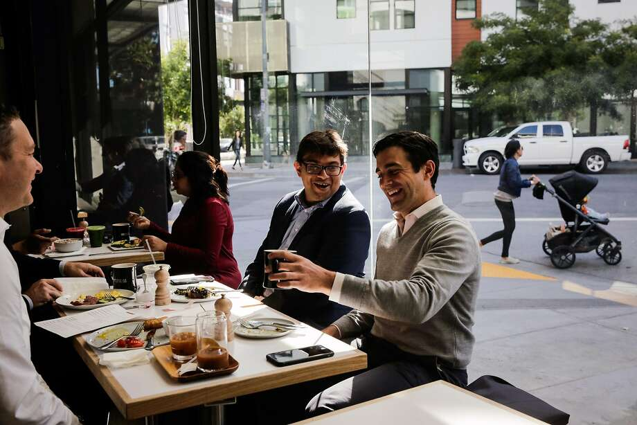 John Hoffman (right) laughs with Hamza Suria (third from left) as they dine with friends, including Dominic Piscitelli (left) at Reveille Coffee. Photo: Gabrielle Lurie, The Chronicle