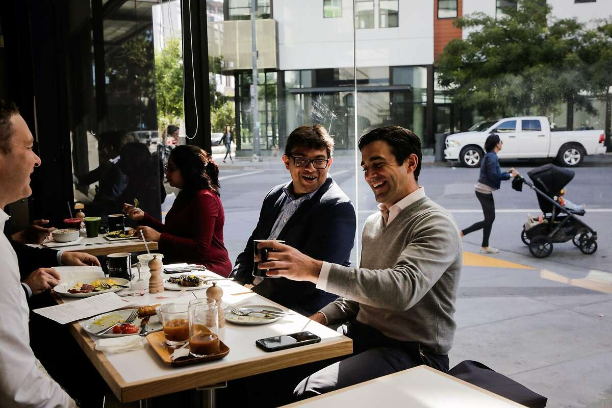 John Hoffman (second from right) laughs with Hamza Suria (third from left) as they dine with friends Jesse Chase (not pictured) and Dominic Piscitelli (left) at Reveille Coffee on Fourth and Long Bridge Streets in Mission Bay in San Francisco, Calif., on Wednesday, July 12, 2017.