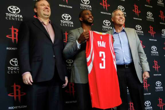 Point guard Chris Paul holds up his Rockets jersey -No. 3, of course - while sandwiched between GM Daryl Morey, left, and coach Mike D'Antoni on Friday.