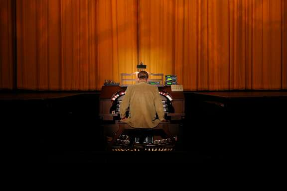 David Hegarty sits down at the theater organ at the Castro getting ready to play music.