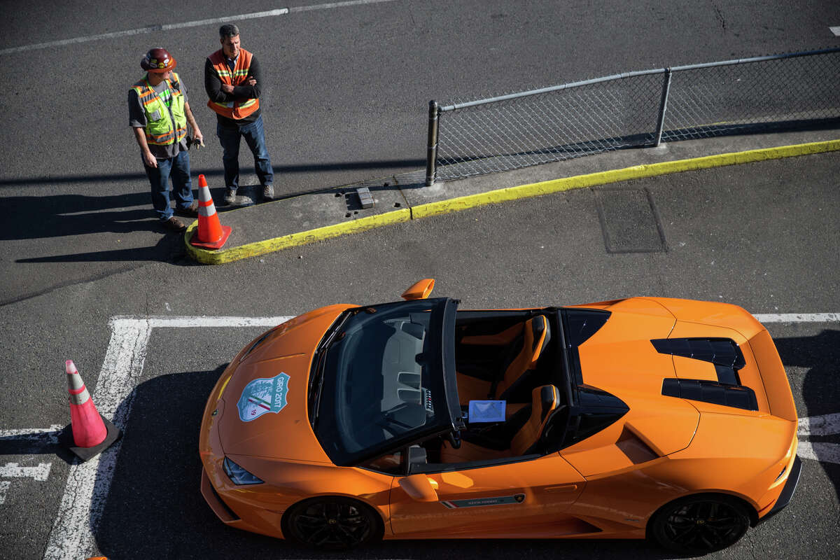 Construction workers check out a Lamborghini Huracán as the two dozen cars wait for a ferry.