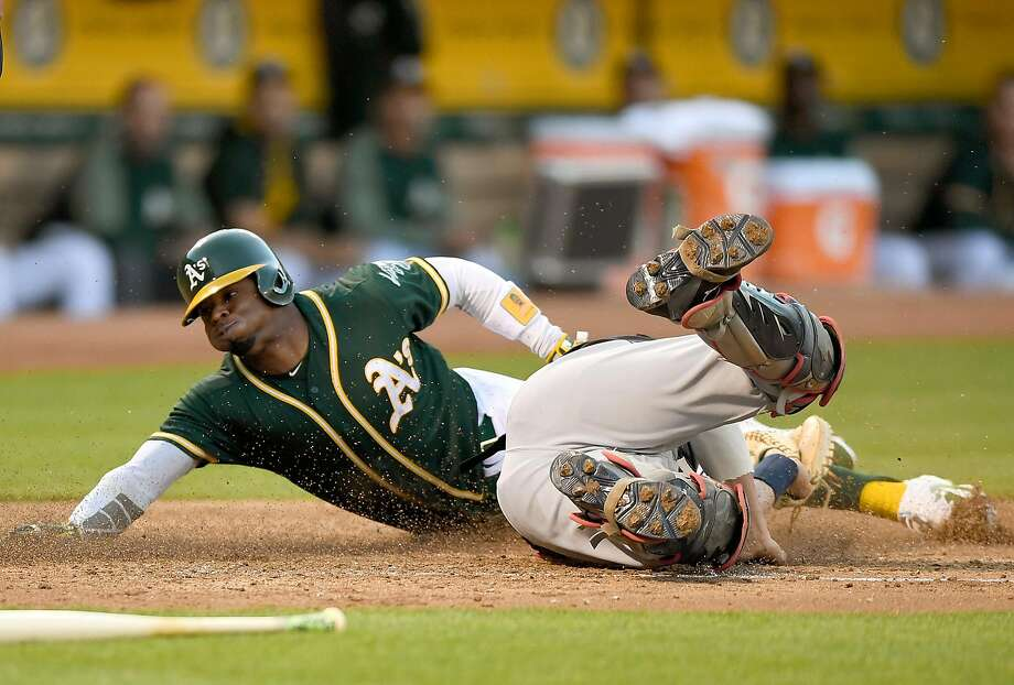 OAKLAND, CA - JULY 14:  Rajai Davis #11 of the Oakland Athletics scores sliding past the tag of Yan Gomes #7 of the Cleveland Indians in the bottom of the third inning at Oakland Alameda Coliseum on July 14, 2017 in Oakland, California.  (Photo by Thearon W. Henderson/Getty Images) Photo: Thearon W. Henderson, Getty Images