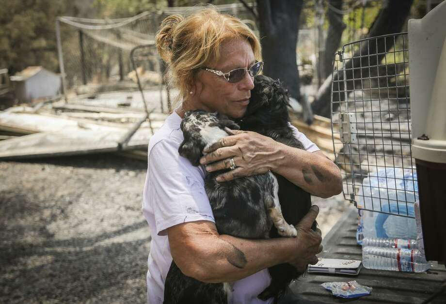 Donna Campos hugs her dogs Gracie Lou (left) and Lola (right) days after losing her property in the Wall Fire near Oroville. She has lived in the area for 30 years and lived in her house for 10 years. Photo: Gabrielle Lurie / Gabrielle Lurie / The Chronicle / ONLINE_YES