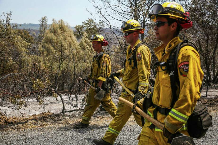 Firefighters Antonio Trapozzano (left), Doyle Biswell and Alex Corral walk back to their engine after checking on hot spots at the Wall Fire in Oroville. Photo: Gabrielle Lurie / Gabrielle Lurie / The Chronicle / ONLINE_YES
