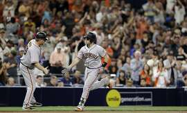San Francisco Giants' Buster Posey is greeted by third base coach Phil Nevin after Posey's home run during the seventh inning of the tema's baseball game against the San Diego Padres on Friday, July 14, 2017, in San Diego. (AP Photo/Gregory Bull)