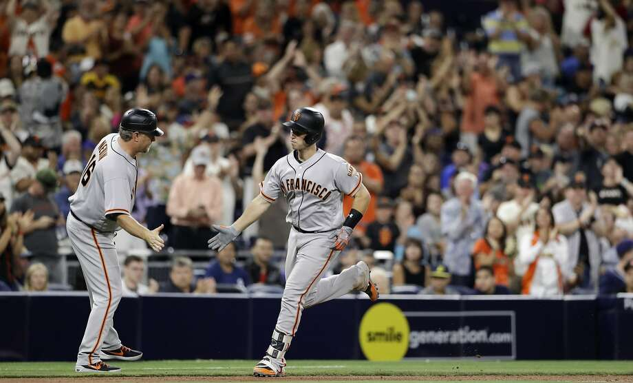 San Francisco Giants' Buster Posey is greeted by third base coach Phil Nevin after Posey's home run during the seventh inning of the tema's baseball game against the San Diego Padres on Friday, July 14, 2017, in San Diego. (AP Photo/Gregory Bull) Photo: Gregory Bull, Associated Press