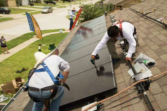 Workers from Alba Solar install panels on a house in Katy. Many solar panels are made in Asia.