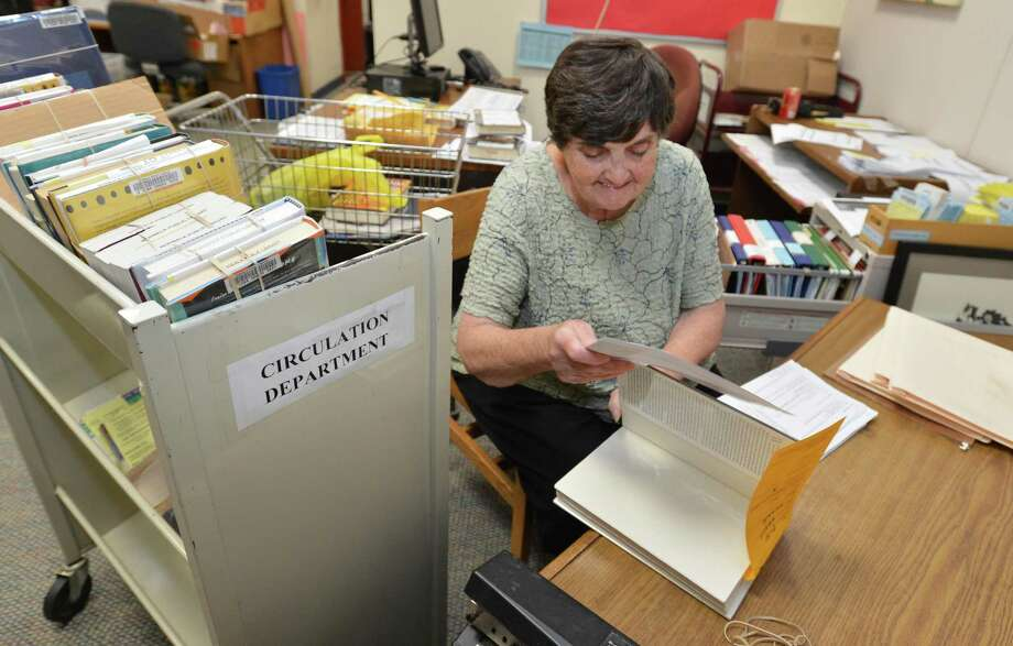 Norwalk Public Library Loan Specialist Vicky Lucarelli works on returning books to other libraries through the statewide library delivery service deliverIT CT on Tuesday. Photo: Alex Von Kleydorff / Hearst Connecticut Media / Norwalk Hour