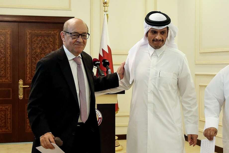 French Minister of Europe and Foreign Affairs Jean-Yves Le Drian (L) embraces his Qatari counterpart Mohammed bin Abdulrahman al-Thani as they walk out of a press conference in the Qatari capital Doha on July 15, 2017. / AFP PHOTO / STRINGERSTRINGER/AFP/Getty Images Photo: STRINGER, AFP/Getty Images
