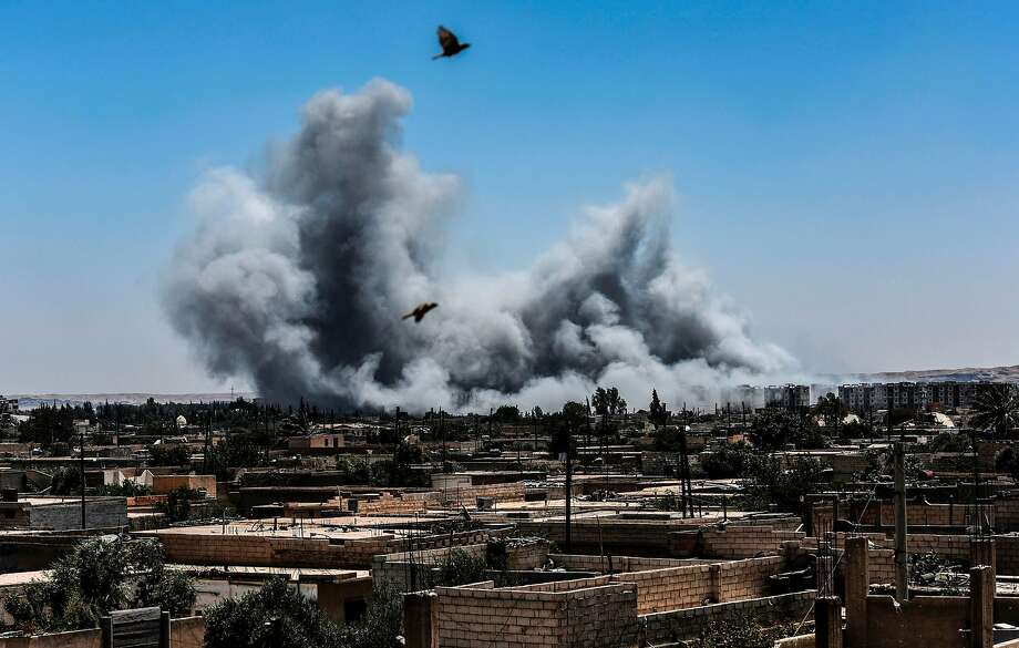 TOPSHOT - Smoke billows following an airstrike on the western frontline of Raqa on July 15, 2017, during an offensive by the Syrian Democratic Forces (SDF), an alliance of Kurdish and Arab fighters, to retake the city from Islamic State (IS) group fighters. The US-backed coalition has captured around 30 percent of Raqa city since it entered the IS bastion in June after a months-long operation to capture territory in the surrounding province. / AFP PHOTO / BULENT KILICBULENT KILIC/AFP/Getty Images Photo: BULENT KILIC, AFP/Getty Images