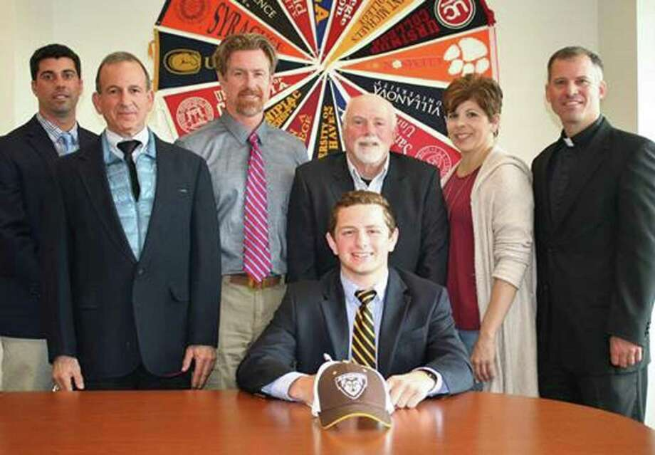 Fairfield Prep senior Evan Titus, pictured front center, has committed to St. Bonaventure University to play Division I Rugby as he begins his college career in the fall of 2017. Joining Titus are, from left, Athletic Director Tom Curran; Principal Dr. Robert Perrotta; Jeffrey Titus; Head Coach Frank Decker; Christine Titus; and Pres. Rev. Tom Simisky, S.J. Titus will study Business and Marketing as well as participate in the Pacioli Scholars Program at St. Bonaventure, a program that focuses on community service and one which will allow him to elaborate on his service work at Prep. Titus has devoted his service energies to assisting special needs children at the New Canaan YMCA for the past two years, and has earned an additional scholarship for his willingness to participate in the service program at St. Bonaventure. During his time as an athlete a Prep, Titus has played four years of rugby and wrestling as well as three years of football. In rugby he is a senior captain as well as the 2017 Northeast Jesuit Rugby Tournament MVP. On the wrestling mat Titus also captained the team along with achieving All-State and All-SCC honors. A consistent hard worker in the classroom, Titus has managed Prep's strong college preparatory course of studies while pursuing his talent in choral music by his participation in Prep's Men's Select Choir for four years. Titus is a resident of Wilton. Photo: John Nash / Hearst Connecticut Media / Norwalk Hour