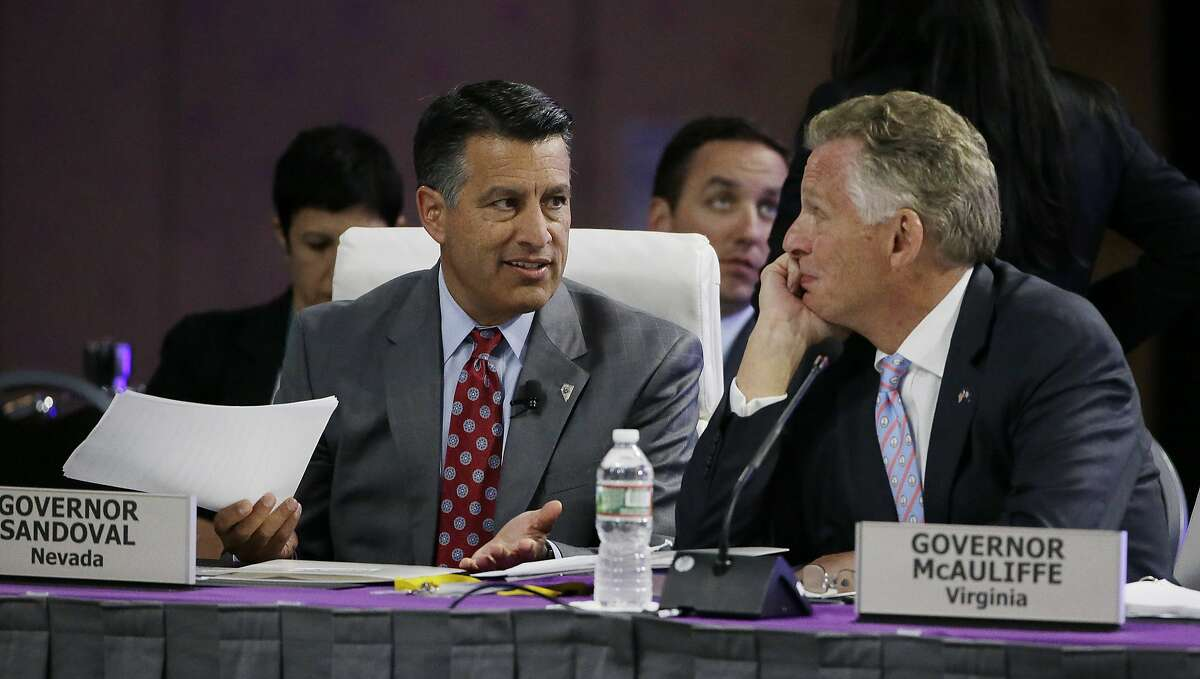 """Nevada Republican Gov. Brian Sandoval, left, and Virginia Democratic Gov. Terence McAuliffe converse before Tesla and SpaceX CEO Elon Musk addresses the closing plenary session entitled """"Introducing the New Chairs Initiative - Ahead of the Curve"""" on the third day of the National Governors Association's meeting Saturday, July 15, 2017, in Providence, R.I. (AP Photo/Stephan Savoia)"""