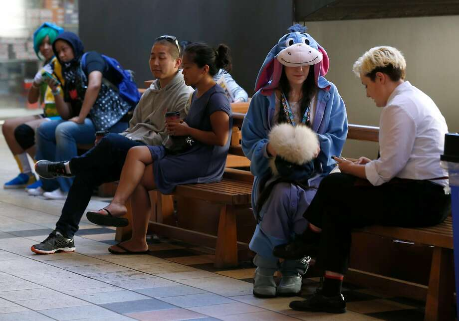 Jenny Jacobitz relaxes in an Eeyore kigurumi while she waits with her friend Tobias Finnian (right) for the start of the annual San Francisco Anime and Cosplay Festival at Japantown in San Francisco. Photo: Paul Chinn, The Chronicle