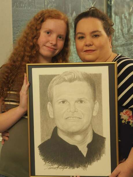 Madison and her mother Katherine Maiorana of Stockdale, who lost Air Force Tech. Sgt. Mark Maiorana in 2003, hold the portrait drawn for them by Michael Reagan, a Washington-based portrait artist who has sketched more than 5,000 etchings of troops who died in the last 14 years. Photo: J.p. Lawrence /
