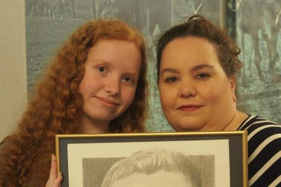 Madison and her mother Katherine Maiorana of Stockdale, who lost Air Force Tech. Sgt. Mark Maiorana in 2003, hold the portrait drawn for them by Michael Reagan, a Washington-based portrait artist who has sketched more than 5,000 etchings of troops who died in the last 14 years.
