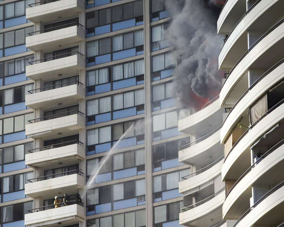 Firefighters on a balcony spray water on a fire burning above their position Friday at the Marco Polo residences in Honolulu. Three people died in the blaze, and at least 12 others were injured. Photo: Marco Garcia, Associated Press