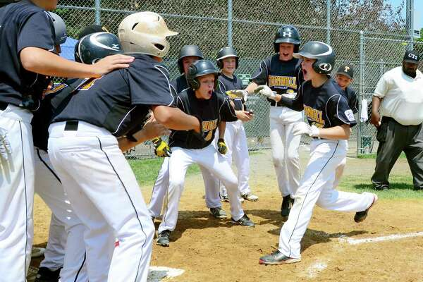 Trumbull's Scott Gell heads to home plate and cheering teammate after hitting a grand slam home run during District 2 little league Championship baseball action against Fairfield National in Trumbull, Conn., on Saturday July 15, 2017.