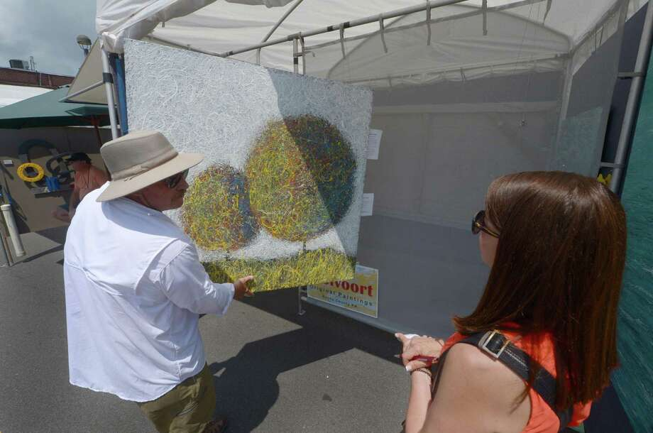 Painter Peter Stolvoort chats with art consultant Mara Arzi during the 44th annual Westport Fine Arts Festival Saturday, July 15, 2017, on Elm Street in Westport, Conn. The Westport Fine Arts Festival featured a premier roster of national and international fine artists across 12 categories and includes over 140 juried artists. Photo: Erik Trautmann / Hearst Connecticut Media / Norwalk Hour