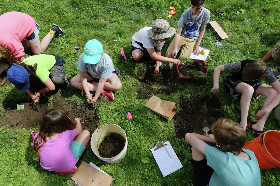 Children taking part in the Albany Archeology Field School put on by archaeologists from Hartgen Archeological Association, Inc., work with trowels as they dig into the earth on Monday, July 10, 2017, in Albany, N.Y.  The children in the week-long camp will be working at the Thomas Elkin's Residence.   Elkins was a 19th Century dentist, abolitionist, inventor, and world traveler.  The archaeological field school provides students the opportunity to learn the scientific techniques of archaeological excavation, artifact cataloging, site survey, and mounting exhibits.    (Paul Buckowski / Times Union) Photo: PAUL BUCKOWSKI / 40040757A