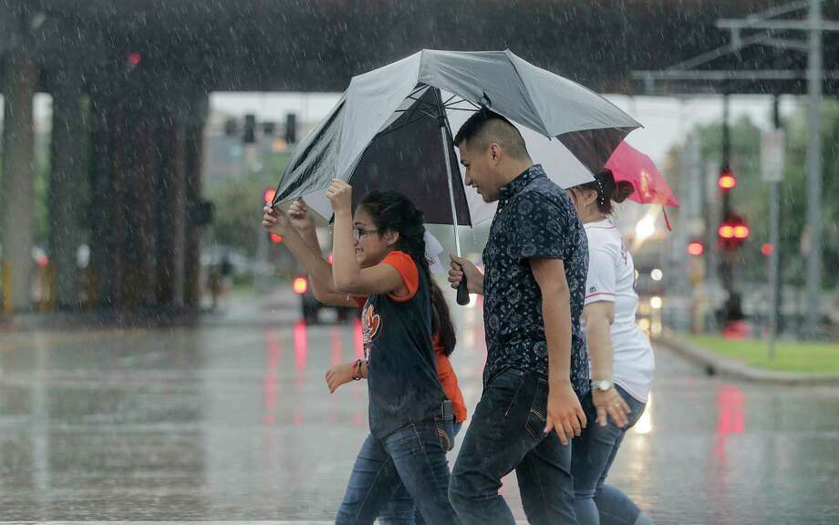 Astros fans keep dry as they walk to Minute Maid Park in the rain on  Saturday, July 15, 2017, in Houston. Photo: Elizabeth Conley, Houston Chronicle / © 2017 Houston Chronicle