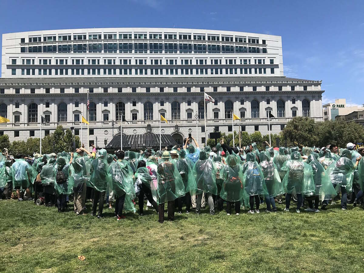 Participants in green ponchos gather at Civic Center Plaza to break the Guinness World Record for the largest human flower.