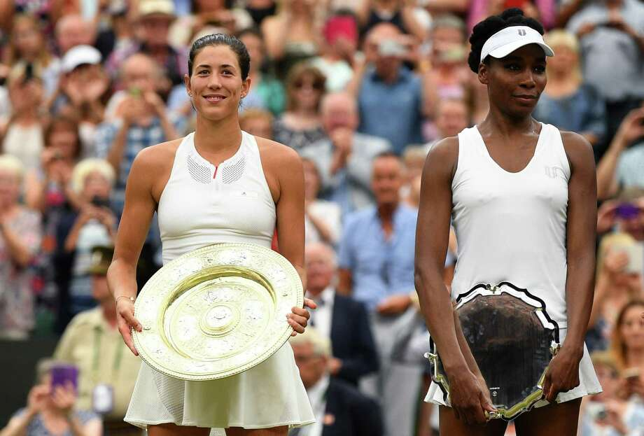 LONDON, ENGLAND - JULY 15:  Garbine Muguruza of Spain celebrates victory with the trophy alongside runner up Venus Williams of The United States after the Ladies Singles final on day twelve of the Wimbledon Lawn Tennis Championships at the All England Lawn Tennis and Croquet Club at Wimbledon on July 15, 2017 in London, England.  (Photo by David Ramos/Getty Images) Photo: David Ramos / Getty Images / 2017 Getty Images