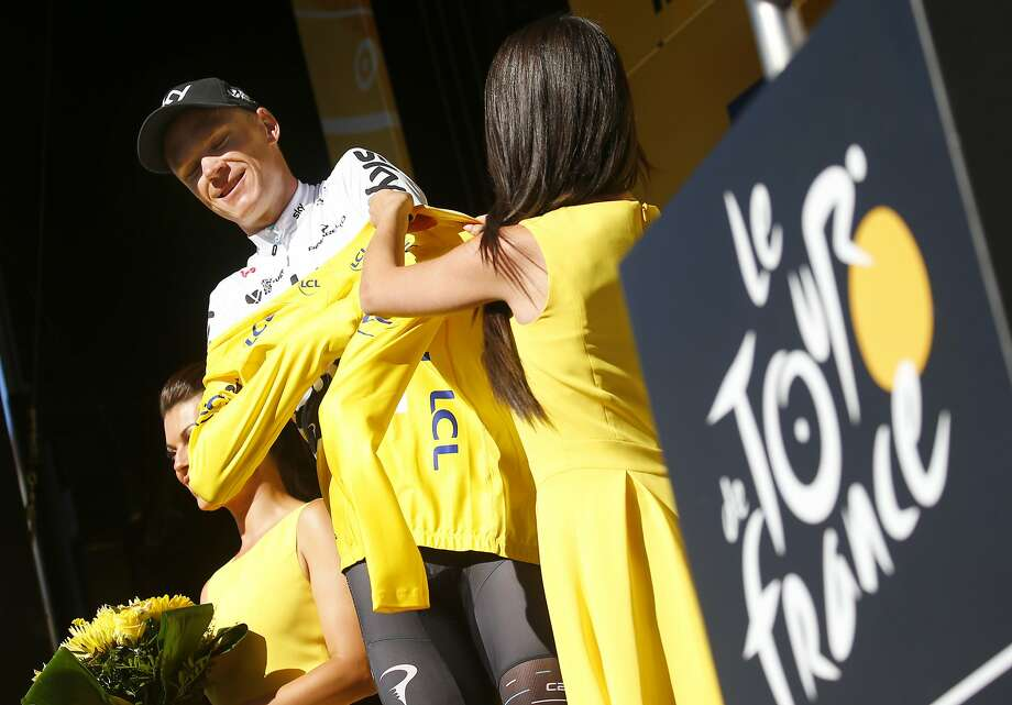 Britain's Chris Froome gets help in putting on the overall leader's yellow jersey. Photo: Peter Dejong, Associated Press