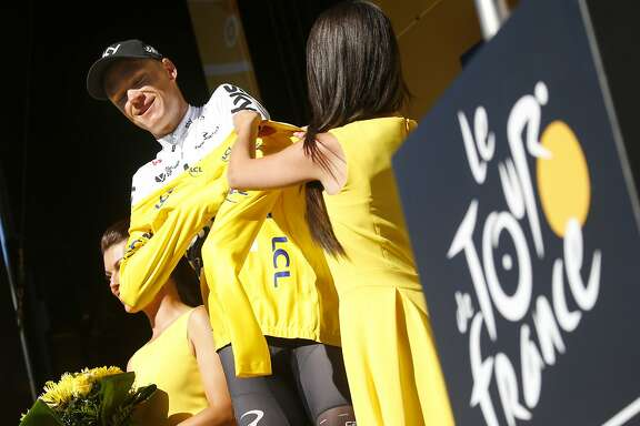 Britain's Chris Froome, puts on the overall leader's yellow jersey, after the fourteenth stage of the Tour de France cycling race over 181.5 kilometers (112.8 miles) with start in Blagnac and finish in Rodez, France, Saturday, July 15, 2017. (AP Photo/Peter Dejong)