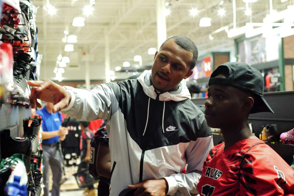 Trevon Conic, right, gets a bit of shoe buying advice from Texans rookie quarterback Deshaun Watson during a shopping spree Friday in Friendswood.
