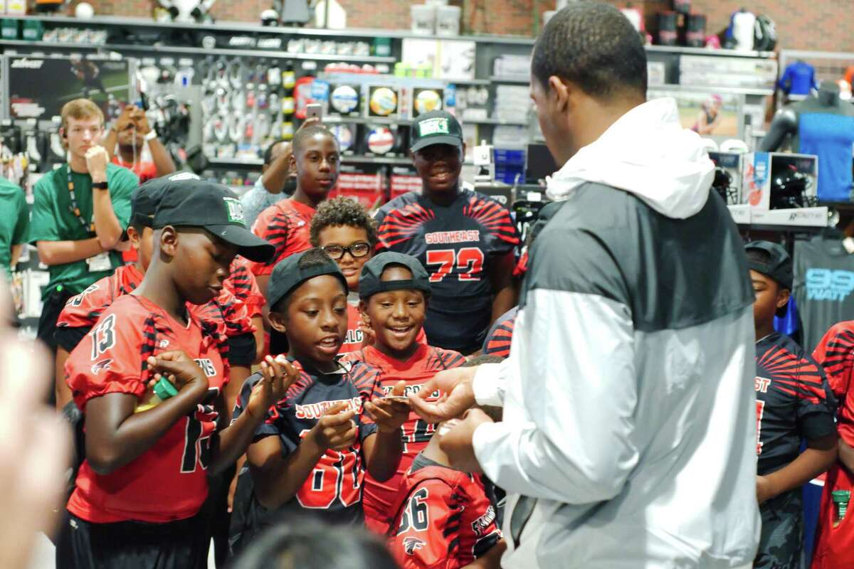 Watson passes out $150 gift cards to members of the Southeast Falcons youth football team Friday at Dick's Sporting Goods.