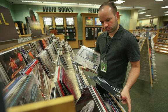 Chris Williams, a history teacher at Stephen F. Austin High School, stocks shelves June 22 in the music section of Barnes & Noble on W. Gray in Houston.