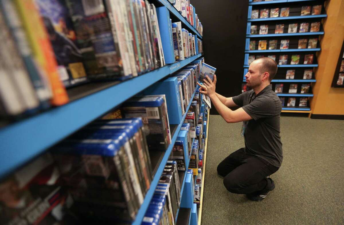 Chris Williams, a history teacher at Houston's Austin High School, stocks shelves in the music section of Barnes & Noble on W. Gray, Thursday, June 22, 2017, in Houston. Williams works part-time at the store to help supplement his income as a teacher. (Mark Mulligan / Houston Chronicle)
