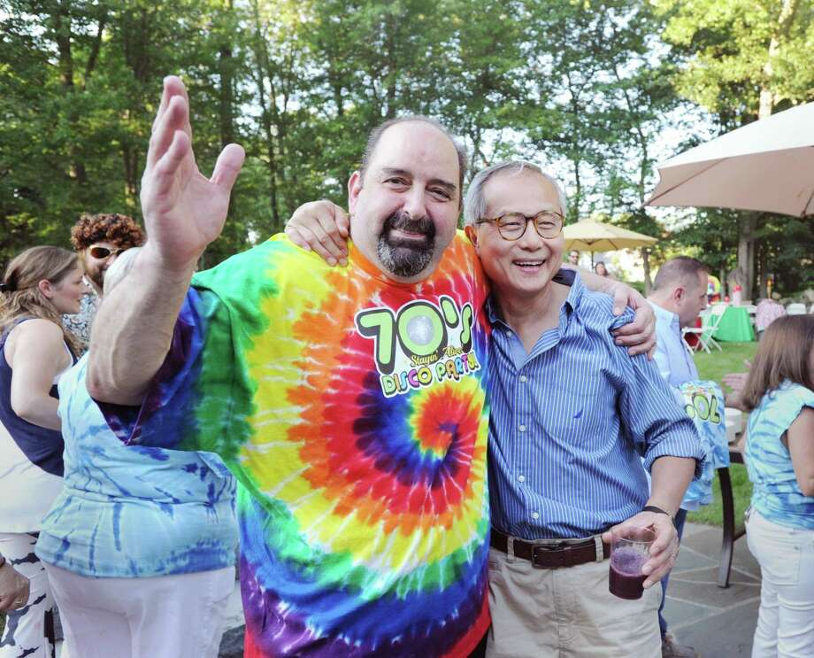 "Cancer survivor Frank Colandro, left, gives a hug to Dr. Steve Lo, Colandro's Stamford Hospital oncologist, during Colandro's 1970s disco-themed party ""Stayin Alive"" at his home in Stamford Saturday night, July 15, 2017. Photo: Bob Luckey Jr. / Hearst Connecticut Media / Greenwich Time"