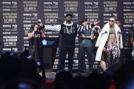 Floyd Mayweather Jr., left, poses as Conor McGregor, of Ireland, right watches during a news conference at Barclays Center Thursday, July 13, 2017, in New York. (AP Photo/Frank Franklin II)