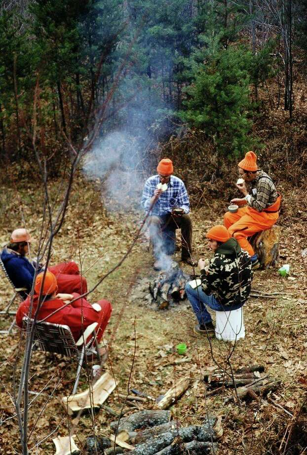 Hunters sit around a deer-camp campfire. (Steve Griffin/file photo for the Daily News)
