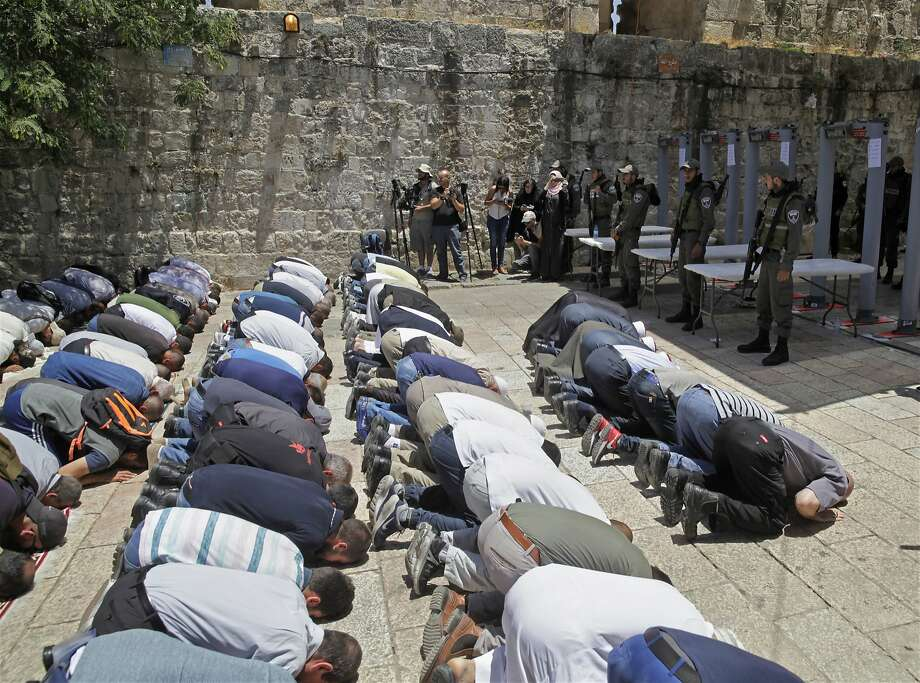 Israeli border police officers stand guard as Muslim men pray outside the Al Aqsa Mosque compound, in Jerusalem Sunday, July 16, 2017. Hundreds of Muslim worshippers visited a Jerusalem holy site Sunday after Israel reopened the compound following a rare closure in response to a deadly shooting last week that raised concerns about wider unrest. (AP Photo/Mahmoud Illean) Photo: Mahmoud Illean, Associated Press