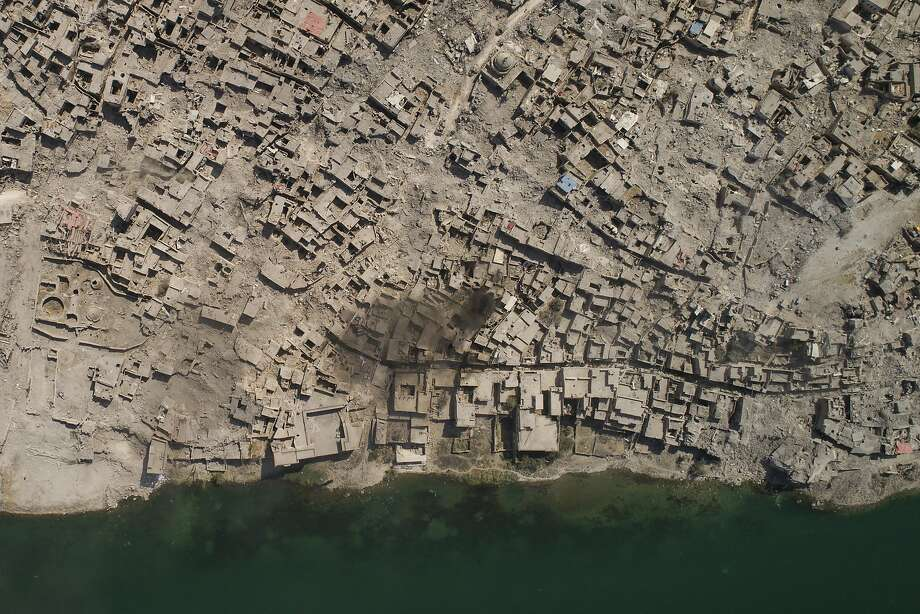 In this July 10, 2017 photo, an aerial view of the Tigris river and the Old City of Mosul, Iraq. Iraq's U.S.-backed forces succeeded in wresting Mosul from the Islamic State group but at the cost of enormous destruction. The nearly 9-month fight culminated in a crescendo of devastation _ the blasting of the historic Old City to root out the militants' final pockets. (AP Photo/Felipe Dana) Photo: Felipe Dana, Associated Press