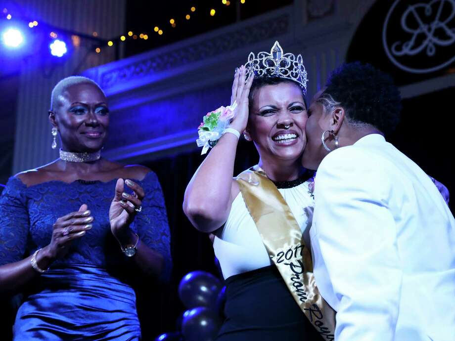 Liz Heck, left, receives a kiss from girlfriend Sabrina Oliver  on the stage after being crowned one of the two prom royal at Houston Gay Prom, an attempt to reclaim what many in the LGBT community missed out on in high school, Saturday, July 15, 2017, in Houston. Photo: Yi-Chin Lee, Houston Chronicle / © 2017  Houston Chronicle