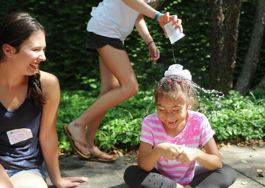 "Rising third-grader Stephanie Molina gets water dumped on her head by volunteer rising senior Katie McClymont during a game of ""Drip, Drip, Drop"" during outdoor snacktime at the Greenwich Academy Talent Enrichment camp. Photo: Tyler Sizemore / Hearst Connecticut Media / Greenwich Time"