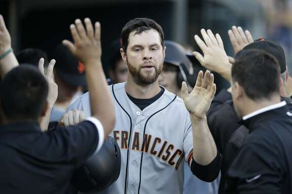 San Francisco Giants first baseman Brandon Belt is greeted in the dugout after scoring during the fourth inning of the team's baseball game against the Detroit Tigers, Wednesday, July 5, 2017, in Detroit. (AP Photo/Carlos Osorio)