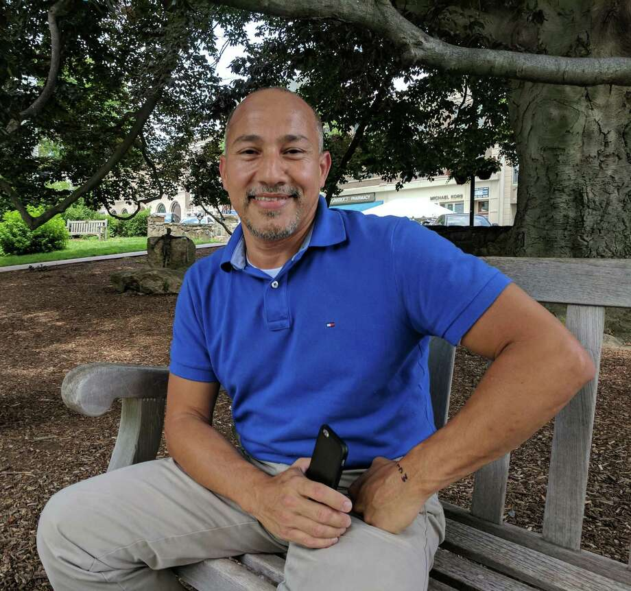 Jorge Ayala enjoyed his lunch break at Greenwich Commons, wondering what it would be like if there were a public swimming pool where the square plot of grass is. Photo: Jennifer Turiano / Hearst Media CT