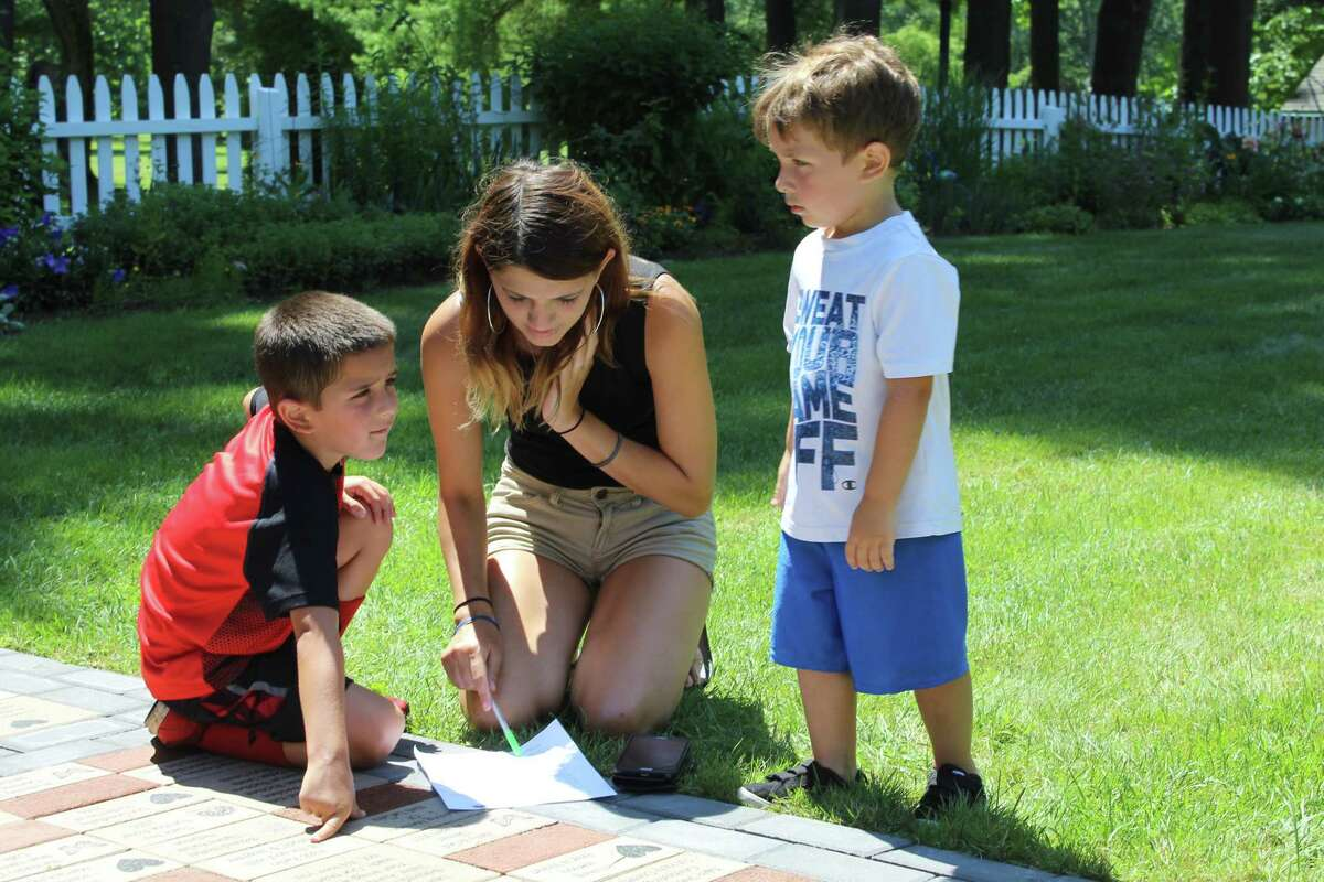 New Milford resident Vanessa Rodgriguez and her sons Julian, 5, left, and Jayden, 3, right, examines the sheet of questions at the Harrybrooke Park scavenger hunt.