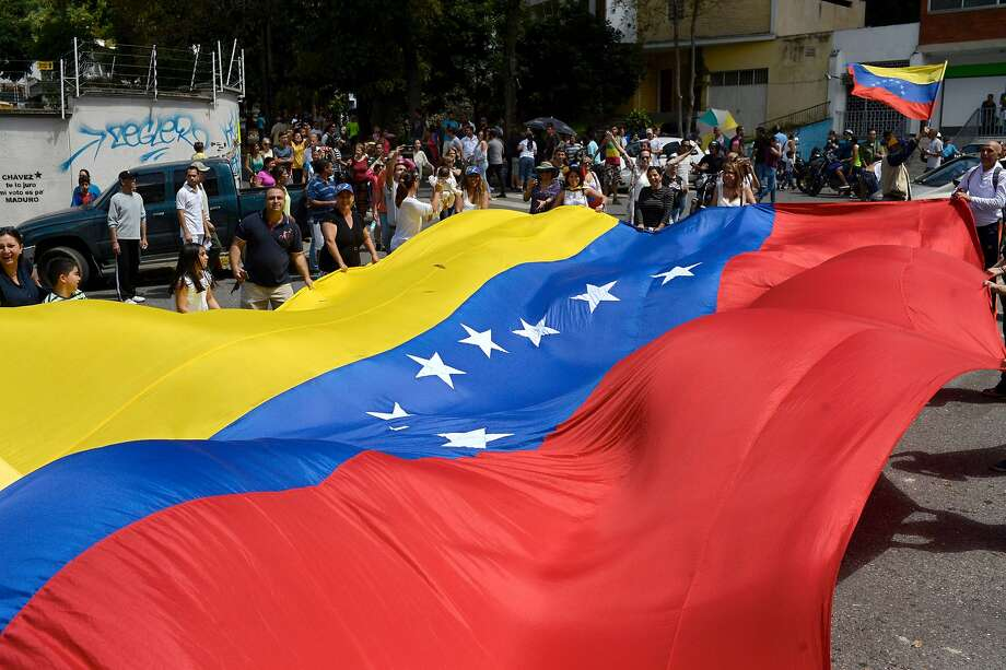 People gather in Caracas on July 16, 2017 during an opposition-organized vote to measure public support for President Nicolas Maduro's plan to rewrite the constitution. Authorities have refused to greenlight the vote that has been presented as an act of civil disobedience and supporters of Maduro are boycotting it. Protests against Maduro since April 1 have brought thousands to the streets demanding elections, but has also left 95 people dead, according to an official toll.  / AFP PHOTO / FEDERICO PARRAFEDERICO PARRA/AFP/Getty Images Photo: FEDERICO PARRA, AFP/Getty Images