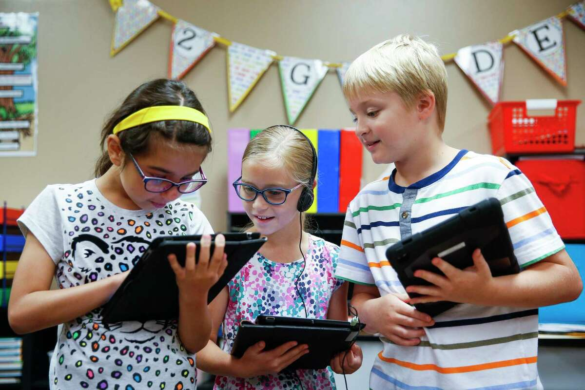 Buckalew Elementary School second graders Amanda McBride, left, Anna Alexander, center, and Carter Schmitt work on their grammar with an iPad application Thursday, May 18, 2017 in Conroe. Buckalew Elementary School is the top ranking elementary school in the greater Houston area in the 2017 Children at Risk Annual School rankings. ( Michael Ciaglo / Houston Chronicle )
