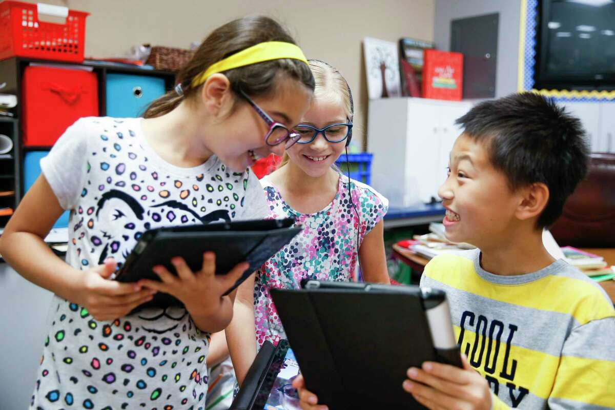Buckalew Elementary School second graders Amanda McBride, left, Anna Alexander, center, and Howell Zhou work on their grammar with an iPad application Thursday, May 18, 2017 in Conroe. Buckalew Elementary School is the top ranking elementary school in the greater Houston area in the 2017 Children at Risk Annual School rankings. ( Michael Ciaglo / Houston Chronicle )