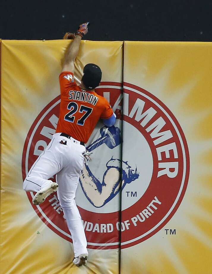 Miami Marlins right fielder Giancarlo Stanton loses his glove over the wall as he attempted to catch a triple hit by Los Angeles Dodgers' Chris Taylor during the fourth inning of a baseball game, Sunday, July 16, 2017, in Miami. The Dodgers defeated the Marlins 3-2. When Stanton made a running leap and stretched his left arm above the wall, his glove came off and fell to the other side. (AP Photo/Wilfredo Lee) Photo: Wilfredo Lee, Associated Press